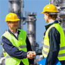 Two men wearing hard hats and bright yellow-green vests shaking hands at a chemical facility.