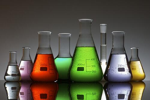 Chemical beakers of different sizes holding liquid of different colors.