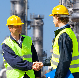 Two men wearing neon green vests and yellow hard hats shaking hands at a chemical facility.
