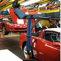 Cars on a conveyor system in a manufacturing plant.