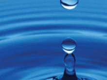 Drop of water after it has hit a body of water with droplets in the air and ripples flowing out from the epicenter.